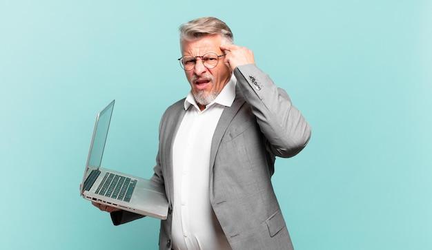 Starszy biznesmen czuje się zdezorientowany i zdezorientowany, pokazując, że jesteś szalony, szalony lub oszalały