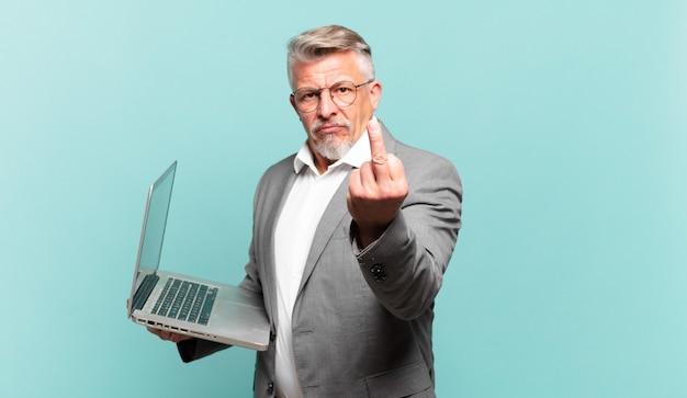 Starszy biznesmen czuje się zły, zirytowany, buntowniczy i agresywny, machając środkowym palcem, walczący