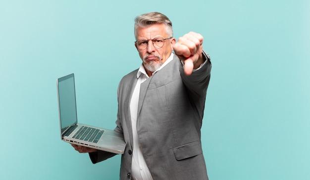 Starszy biznesmen czuje się zły, zły, zirytowany, rozczarowany lub niezadowolony, pokazując kciuk w dół z poważnym spojrzeniem
