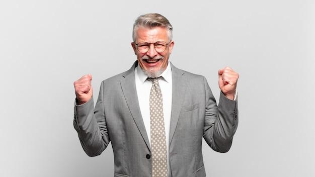 Starszy biznesmen czuje się zszokowany, podekscytowany i szczęśliwy, śmiejąc się i świętując sukces, mówiąc wow!