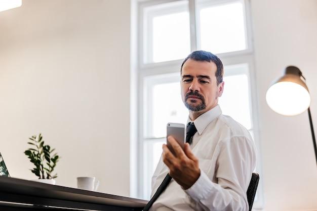 Starszy biznesmen czyta wiadomość na jego telefonie komórkowym w biurze.
