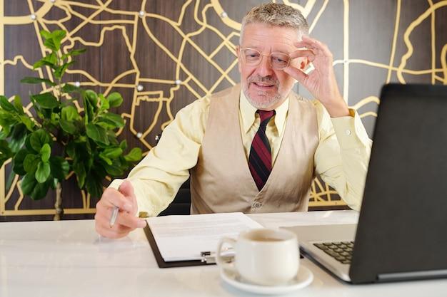 Starszy biznesmen dostosowywanie okularów i czytanie umowy biznesowej, gdy siedzisz przy stoliku kawiarnianym