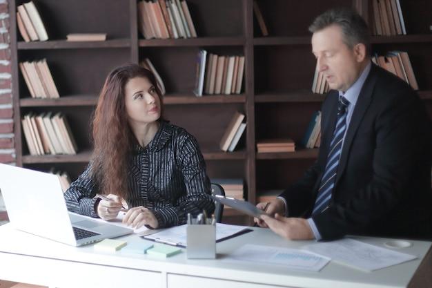 Starszy biznesmen i asystent pracujący w nowoczesnym biurze.