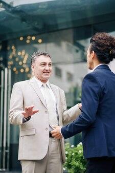 Starszy biznesmen i jego kolega stoją przed budynkiem biurowym i omawiają najnowsze informacje na temat udanego projektu