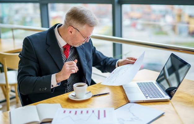 Starszy biznesmen korzysta z laptopa i robi notatki, siedząc w nowoczesnym biurze