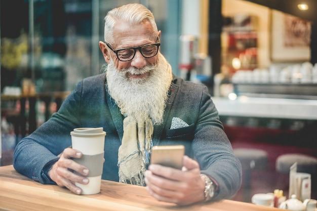 Starszy biznesmen korzystający z aplikacji na smartfona podczas picia kawy w kawiarni-barze - modny przedsiębiorca robi śniadanie - praca, poranna przerwa i koncepcja techniczna - okno z zewnątrz - skupienie na twarzy