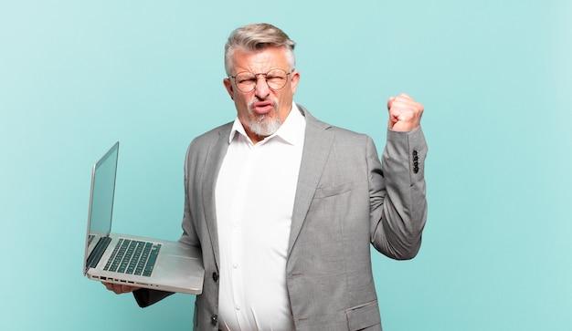 Starszy biznesmen krzyczy agresywnie z gniewnym wyrazem twarzy lub z zaciśniętymi pięściami świętuje sukces
