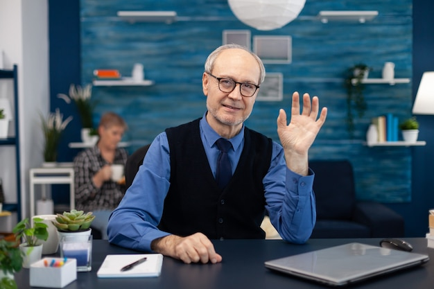 Starszy biznesmen machający do kamery w okularach podczas rozmowy wideo