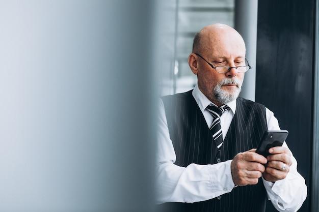 Starszy biznesmen opowiada na telefonie przy biurem