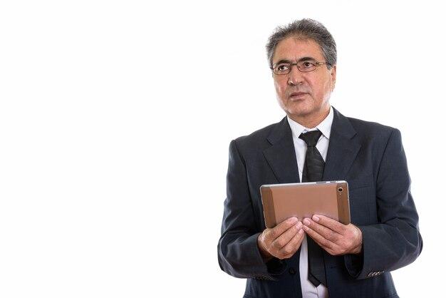 Starszy biznesmen perski posiadający cyfrowy tablet i patrząc na copyspace