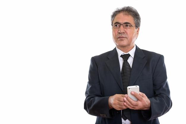 Starszy biznesmen perski posiadający telefon komórkowy i patrząc na copyspace