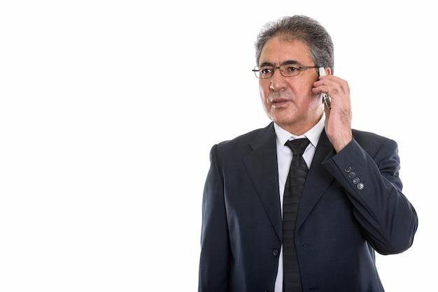 Starszy biznesmen perski rozmawia przez telefon komórkowy