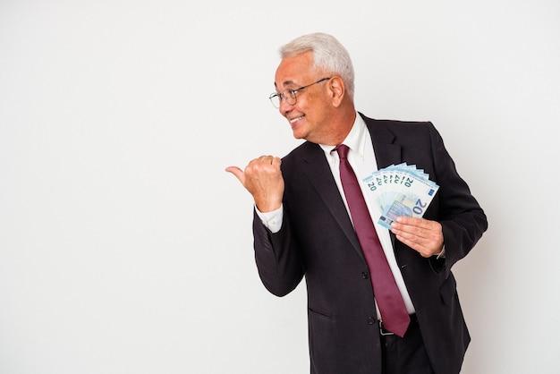 Starszy biznesmen posiadający rachunki na białym tle punkty z palcem od kciuka, śmiejąc się i beztroski.