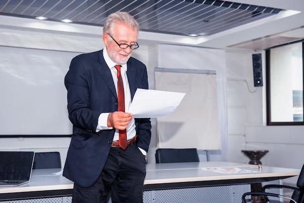 Starszy biznesmen pracujący w biurze. patrząc na wykres zysków biznesowych na papierze.