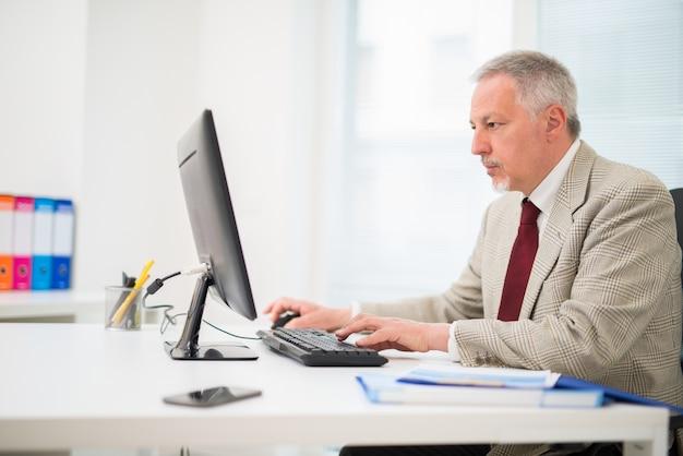 Starszy biznesmen pracuje na jego komputerze