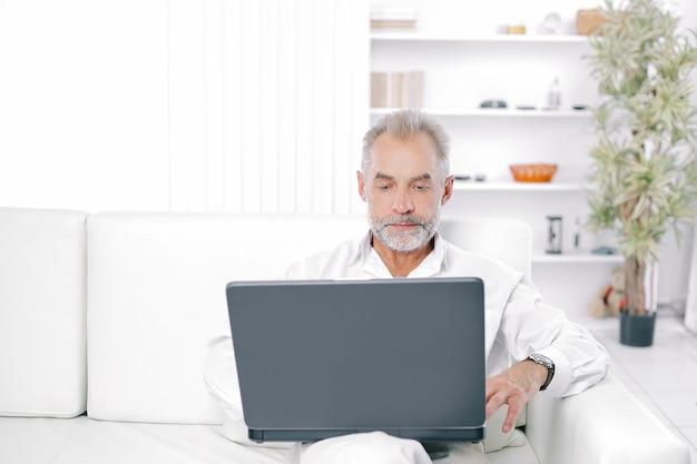 Starszy biznesmen pracuje na laptopie w jego biurze.