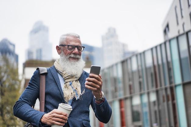 Starszy biznesmen przy użyciu telefonu komórkowego idąc do pracy