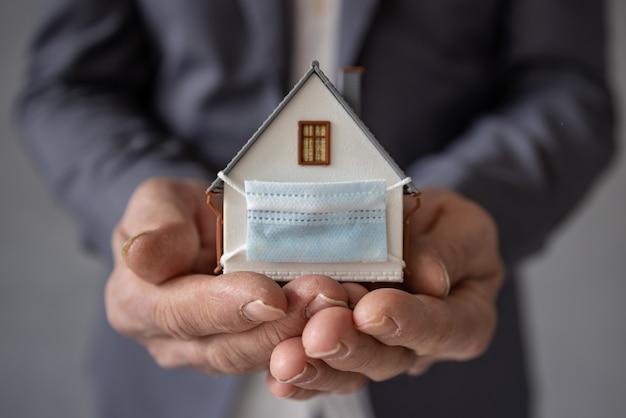 Starszy biznesmen trzyma model domu na sobie ochronną maskę medyczną w rękach. biznes podczas koncepcji pandemii koronawirusa covid-19
