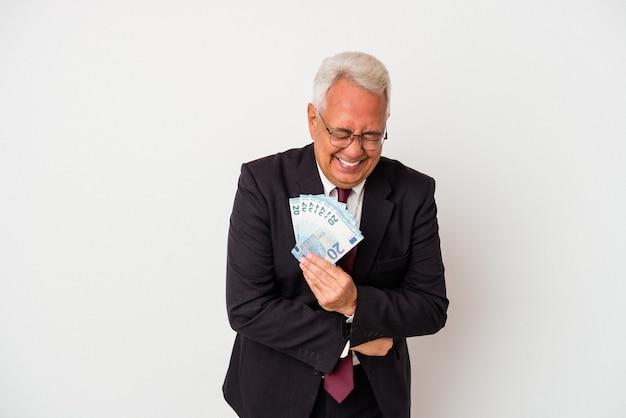 Starszy biznesmen trzymający rachunki odizolowywał śmiać się i bawić.