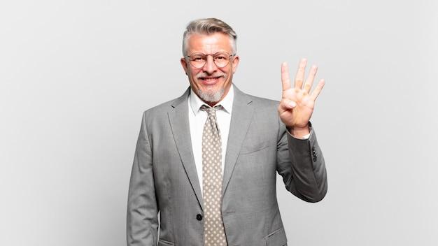 Starszy biznesmen uśmiecha się i wygląda przyjaźnie, pokazując cyfrę cztery lub czwartą z ręką do przodu, odliczając w dół