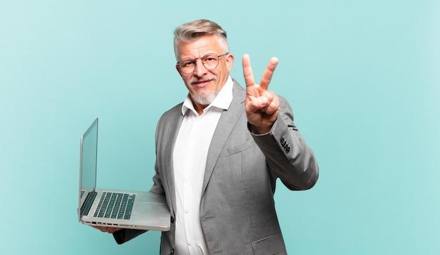 Starszy biznesmen uśmiecha się i wygląda przyjaźnie, pokazując numer dwa lub drugi z ręką do przodu, odliczając w dół