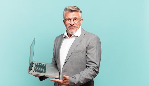 Starszy biznesmen uśmiecha się radośnie, czuje się szczęśliwy i pokazuje koncepcję w przestrzeni kopii z dłonią