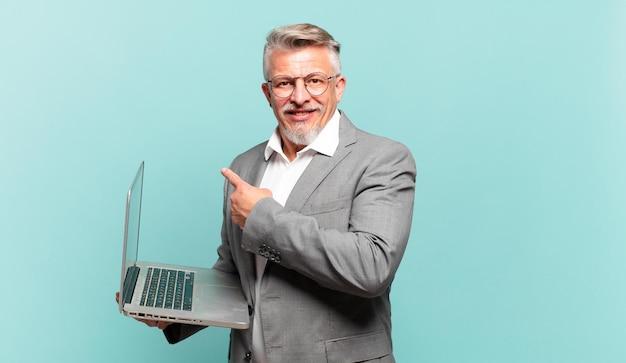 Starszy biznesmen uśmiecha się radośnie, czuje się szczęśliwy i wskazuje na bok i do góry, pokazując obiekt w przestrzeni kopii