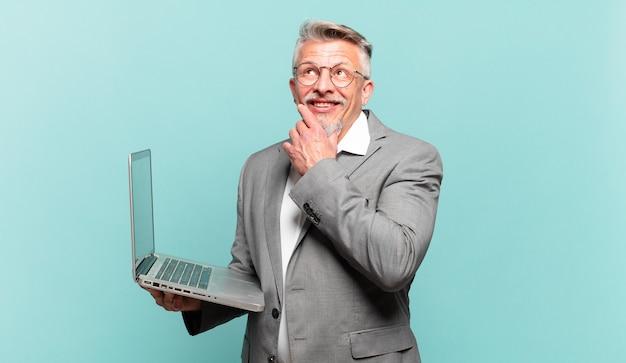 Starszy biznesmen uśmiecha się radośnie i marzy lub wątpi, patrząc w bok