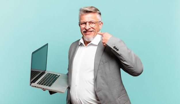 Starszy biznesmen uśmiechający się pewnie, wskazując na własny szeroki uśmiech, pozytywną, zrelaksowaną, usatysfakcjonowaną postawę