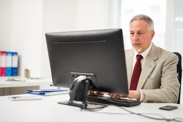 Starszy biznesmen używa jego komputer stacjonarnego