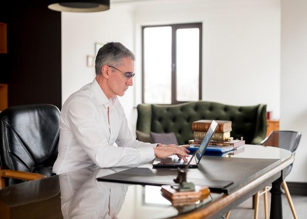 Starszy biznesmen używa jego laptop