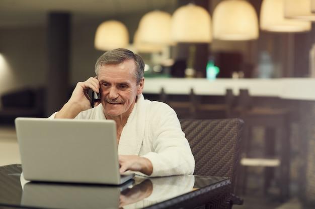 Starszy biznesmen używa laptop w centrum spa
