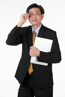 Starszy biznesmen w czarnym garniturze formalne stoisko trzyma okulary i notebooka w ręku patrzeć na kamery. studio strzelać pół ciała z białym tłem. koncepcja dla starszych oczu i problemu wzroku.