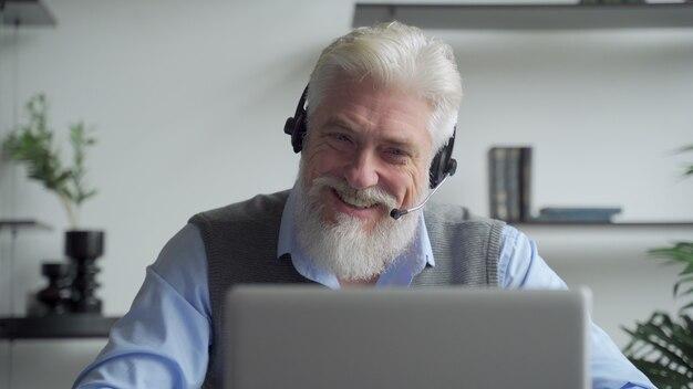 Starszy biznesmen w zestawie słuchawkowym po wideokonferencji z partnerem biznesowym pracującym w biurze