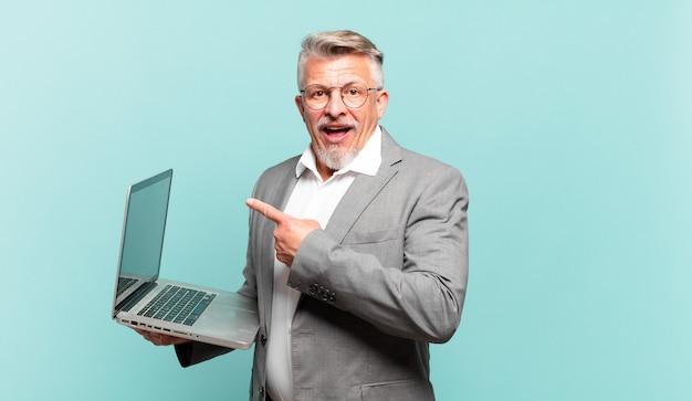 Starszy biznesmen wygląda na podekscytowanego i zaskoczonego, wskazując na bok i w górę, aby skopiować przestrzeń