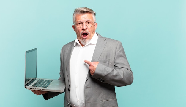 Starszy biznesmen wygląda na zszokowanego i zdziwionego z szeroko otwartymi ustami, wskazując na siebie