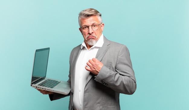 Starszy biznesmen wyglądający arogancko, odnoszący sukcesy, pozytywny i dumny, wskazujący na siebie