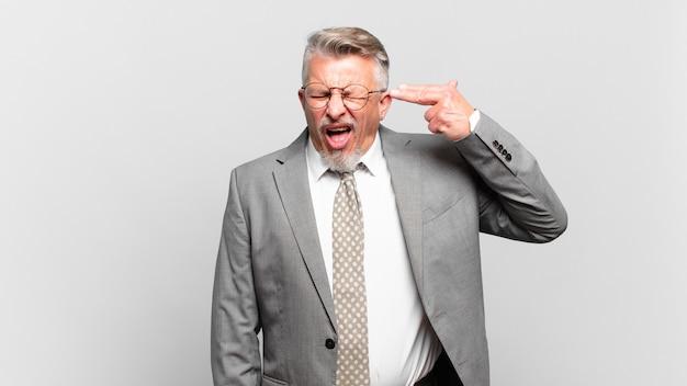 Starszy biznesmen wyglądający na niezadowolonego i zestresowanego, samobójczy gest, robiący znak pistoletu ręką, wskazujący na głowę