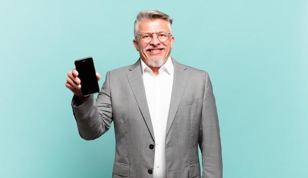 Starszy biznesmen wyglądający na szczęśliwego i mile zaskoczony, podekscytowany zafascynowanym i zszokowanym wyrazem twarzy