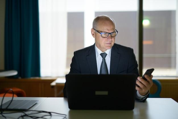Starszy biznesmen za pomocą telefonu i laptopa w pracy w biurze