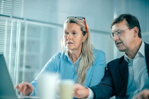 Starszy bizneswoman i jej kolega omawiają wiadomości online. dni robocze w biurze