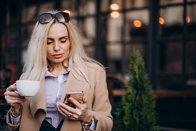 Starszy bizneswoman pije kawę na zewnątrz kawiarni i rozmawia przez telefon