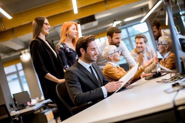 Starszy bizneswoman pracuje wraz z młodymi ludźmi biznesu w biurze