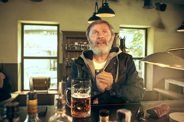 Starszy błagający brodaty mężczyzna pije alkohol w pubie i ogląda program sportowy w telewizji. cieszę się moją ulubioną herbatą i piwem. mężczyzna z kuflem piwa siedzi przy stole. fan piłki nożnej lub sportu. ludzkie emocje