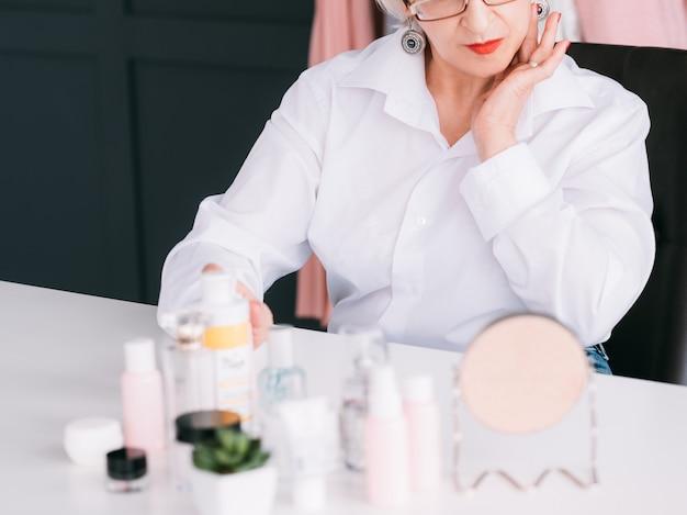 Starszy bloger kosmetyczny. starsza kobieta robiąca recenzję wideo