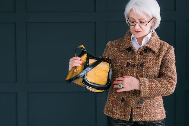 Starszy bloger stylista mody. starsza pani w modnym jesiennym stroju strzelająca do vloga.