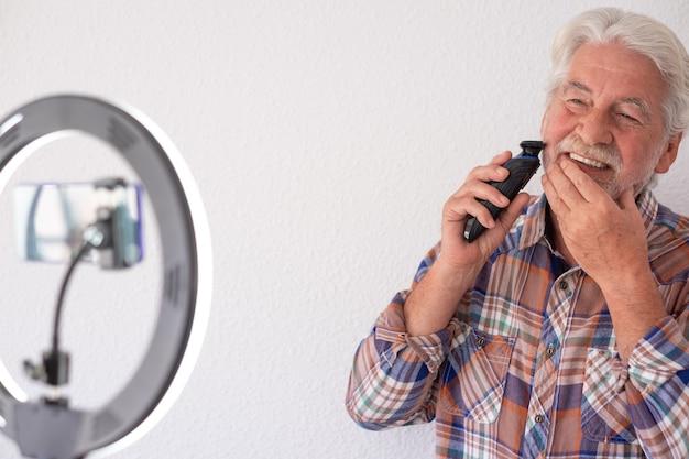 Starszy bloger z nagrywaniem wideo podczas golenia. siwowłosa i broda, białe tło