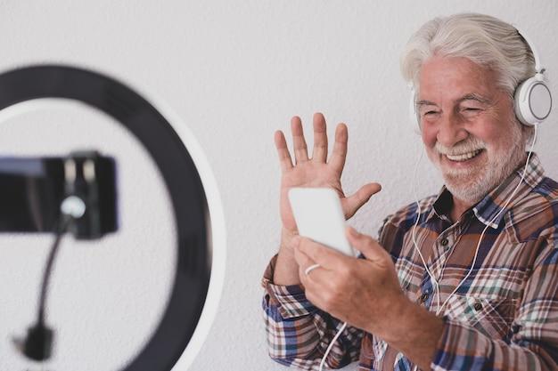 Starszy bloger z nagrywaniem wideo podczas mobilnej rozmowy wideo. białe włosy i broda, białe tło