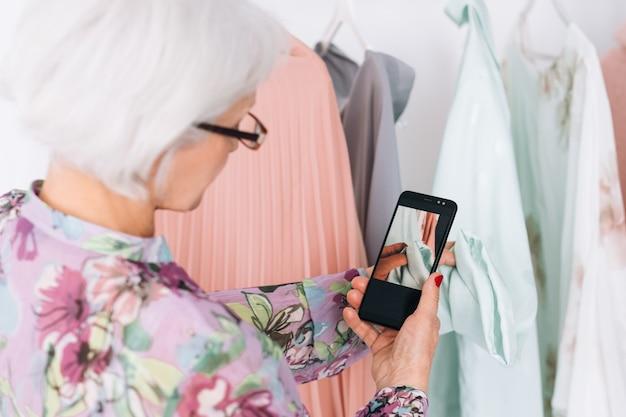 Starszy blogerka modowa dama. modny styl życia. starsza kobieta biorąc mobilne zdjęcie odzieży w salonie.