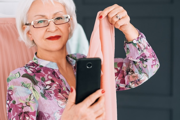 Starszy blogerka modowa dama. modny styl życia. starsza kobieta biorąc selfie analizując typ koloru.